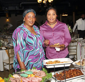 Women Standing in Front of a Birthday Buffet - Birthday Party Venues